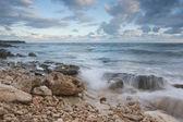 Beautiful rocky sea beach at the sunset — Стоковое фото
