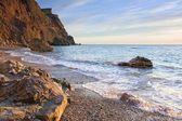 Una hermosa playa con piedras reflejan la luz del sol al atardecer — Foto de Stock