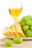 A glass of white wine, sliced cheese and ​​green grapes on wood — Stock Photo