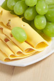 Sliced cheese and green grapes on wood — Stock Photo
