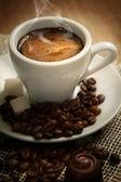 Tazzina di caffè forte su uno sfondo marrone con chicchi di caffè — Foto Stock