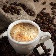 Small cup of strong coffee on brown background with coffee beans — Stock Photo #9065494