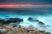 Beautiful rocky sea beach at the sunset — Stock Photo