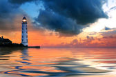 Beautiful nightly seascape with lighthouse and moody sky at the sunset — Stock Photo