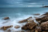 Costa di belle mare con il faro al tramonto — Foto Stock