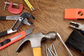 Assorted work tools on wooden panel — Stock Photo