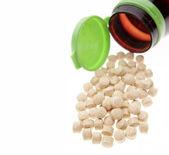 Pills spilling from bottle on plain background — Stock Photo