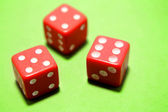 Three dice on green background — Stock Photo