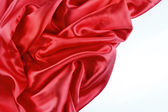 Red silk fabric on plain background — Stock Photo