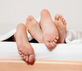 Feet of a couple in bed. — Stock Photo