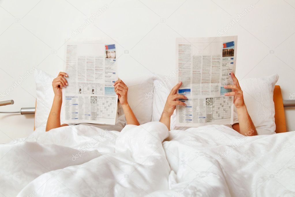 Couple reading a newspaper in bed — Stock Photo #10000943