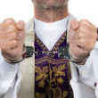 Stock Photo: Catholic priest in handcuffs. abuse