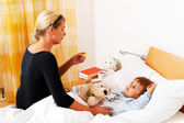 Mother and sick child in bed. — Stock Photo