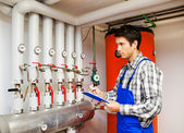 Heating engineer in the boiler room — Stock Photo