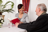 Senior woman reads from a book. — Stock Photo