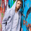 Cool-looking young man in front of graffiti - Stock Photo