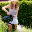 Woman pouring flowers in the garden with watering can - Stockfoto