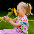 Child with a sunflower in the garden in summer — Stock Photo #10581865