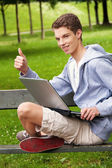 Teenager with laptop outdoors — Stock Photo