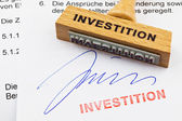 Wood stamp on the document: investment — Stock Photo