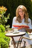读一本书在庭院里的女人 — 图库照片