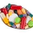 Tablets and medicines on spoon — Stock Photo
