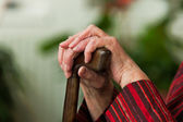 Handicapped elderly woman with a walking cane — Stock Photo