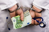 A doctor with euro bank notes and handcuffs — Photo