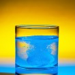 Tablet dissolves in water on glass — Stock Photo