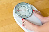 Feet of a woman on bathroom scales — Stock Photo