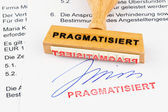 Wooden stamp on the document: pragmatized — Stock Photo