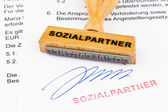Wooden stamp on the document: the social partners — Stock Photo