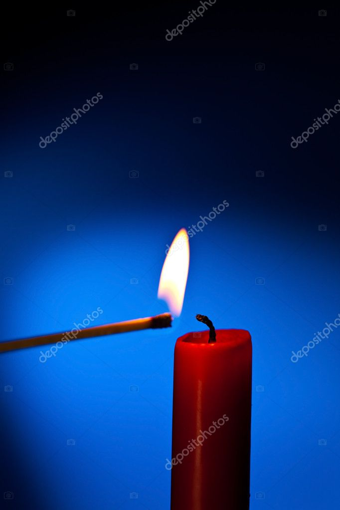 A red candle is lit with a match.  Stock Photo #8166713