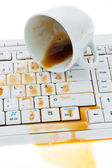 Empty coffee cup on computer keyboard — Stock Photo
