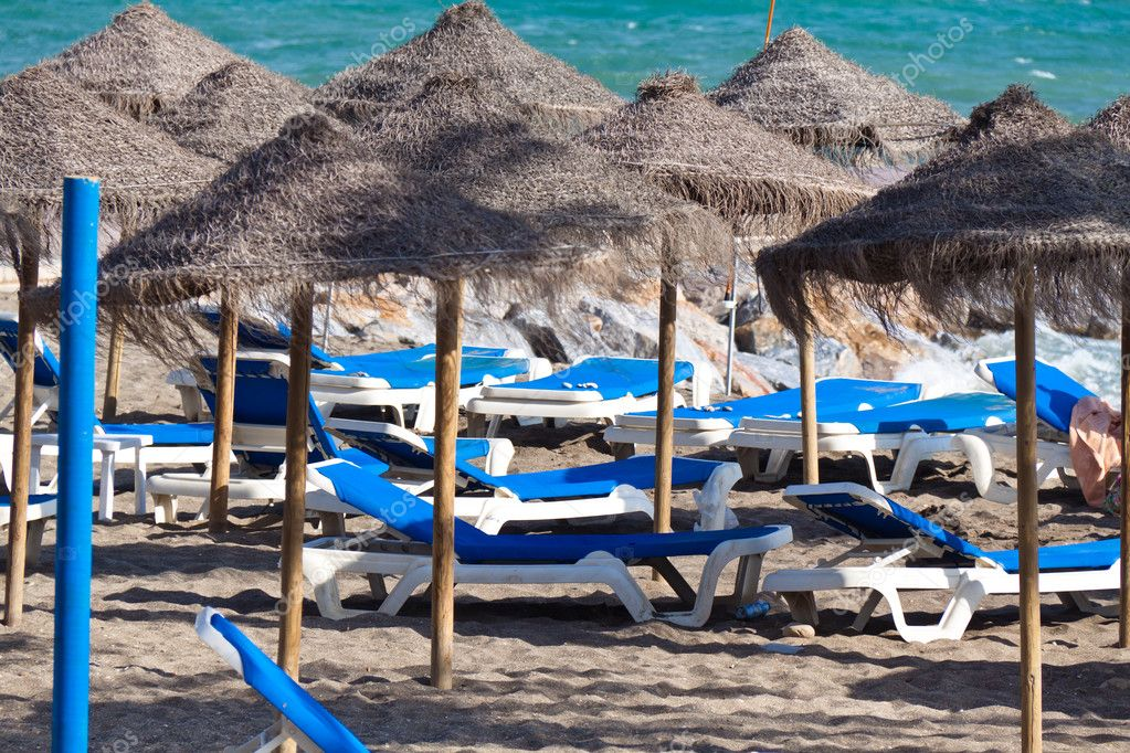 Empty deck chairs on a sandy beach by the sea in spain.  Stock Photo #8175457