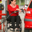 Handicapped woman refuel car at gas station - Stok fotoğraf