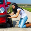 Woman with a flat tire on car - Stockfoto
