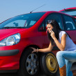 Woman with a flat tire on car — Stock Photo