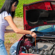Mrs. measures the oil pressure in her car — Stock Photo #8186157