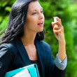 Business woman using mouth spray — Stock Photo