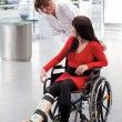 Woman with leg in plaster, wheelchair and carer — Stock Photo