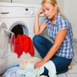 Housewife with washing machine and laundry — Stock Photo