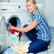 Housewife with washing machine and laundry - Stock Photo