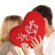 Stockfoto: Couple in love kissing behind a heart.