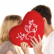 Couple in love kissing behind a heart. — Stock Photo