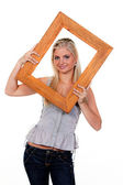 Woman looking through a picture frame — Stock Photo