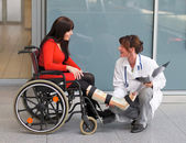 Woman with leg in plaster, a physician and chair — Stock Photo