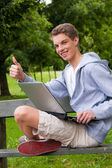 Young man with laptop computer outdoors — Stock Photo
