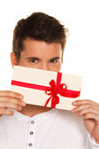 Man with a gift voucher in hand — Stock Photo