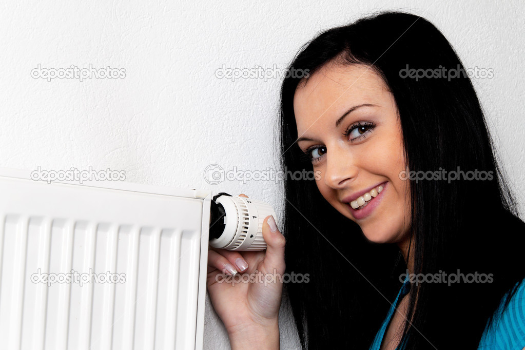 Woman with a heating radiator and thermostat — Stock Photo #8186250